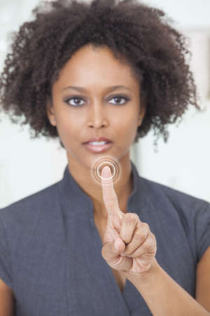 An African American female woman or businesswoman finger raised pushing a button using a touchscreen. The focus is on her finger. photo
