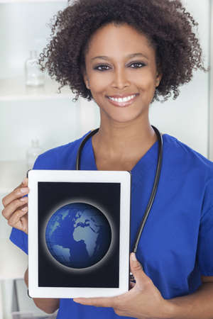 An African American female woman medical doctor with a tablet computer in hospital with a world map or globe on the screen  Stock Photo
