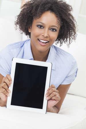 Una ni�a de raza negra o mujer joven que muestra la pantalla mientras se utiliza un ordenador tableta