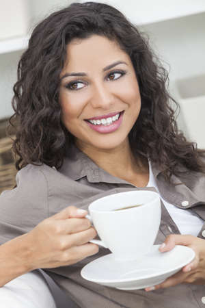 Beautiful young Latina Hispanic woman smiling, relaxing and drinking a cup of coffee or tea Stock Photo - 16782675