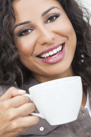 Beautiful young Latina Hispanic woman smiling, relaxing and drinking a cup of coffee or tea photo
