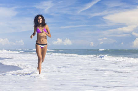 A sexy young brunette woman or girl wearing a bikini running through the surf on a deserted tropical beach with a blue sky  Stock Photo - 16782641