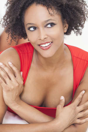 A beautiful sexy mixed race African American girl or young woman laying down wearing a red dress Stock Photo - 16799780