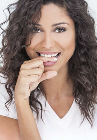 Studio portrait of a beautiful young mixed race Latina Hispanic woman smiling and biting her finger with perfect teeth photo