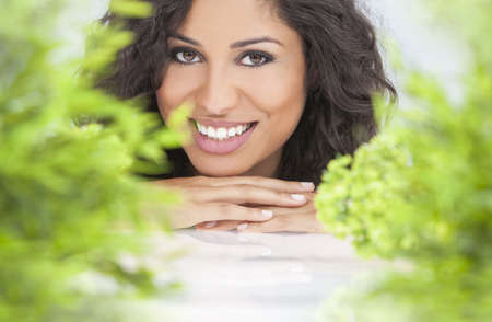 Health spa nature concept studio portrait of a beautiful young woman or girl resting on her hands smiling through natural green leaves Stock Photo - 16799785