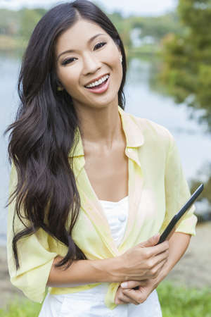 sexy asian woman: Happy, smiling, beautiful Asian Chinese young woman or girl student outside holding tablet computer