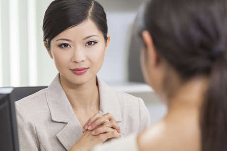 Portrait of a beautiful young Asian Chinese woman or businesswoman in office meeting with female colleague Stock Photo - 17165565