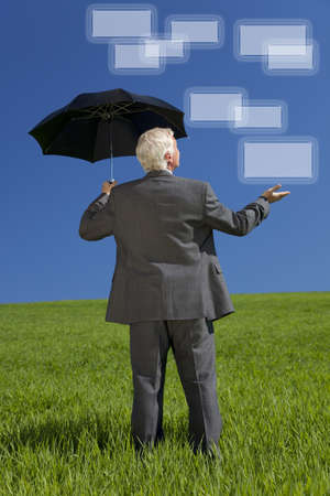 Network concept photograph of a businessman standing in a green field with an umbrella holding out his hand and looking at graphic screen boxes  photo