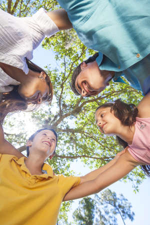 An attractive happy, smiling family of mother, father, son and daughter hugging in a huddle together outside in a park enjoying warm summer sunshine Stock Photo - 17165569