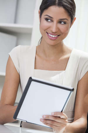 Beautiful young Latina Hispanic woman or businesswoman in an office and using a tablet computer Stock Photo - 17165562