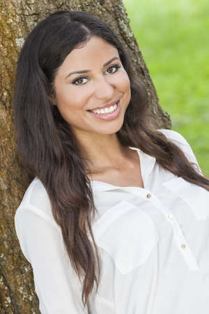 Outdoor portrait of a beautiful young Latina Hispanic woman smiling leaning against a tree Stock Photo - 17165568