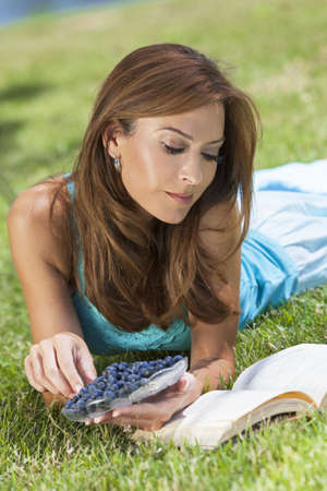A beautiful middle aged woman in her thirties laying down outside on grass eating blueberries and reading a book Stock Photo - 17286187