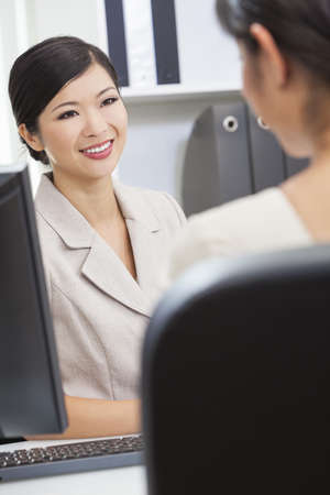 Portrait of a beautiful young Asian Chinese woman or businesswoman in office meeting with female colleague Stock Photo - 17286189