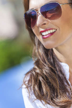 Outdoor portrait of a beautiful young brunette woman in her thirties wearing aviator style sunglasses photo