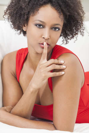 A beautiful mixed race African American girl or young woman wearing a red dress with her finger on her lips asking for silence or keeping a secret Stock Photo - 17286192