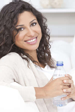 Beautiful young Latina Hispanic woman smiling, relaxing and drinking a bottle of water at home on a sofa Standard-Bild