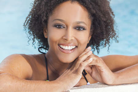 A beautiful sexy young African American girl or young woman wearing a bikini and relaxing on the side of a swimming pool. Stock Photo