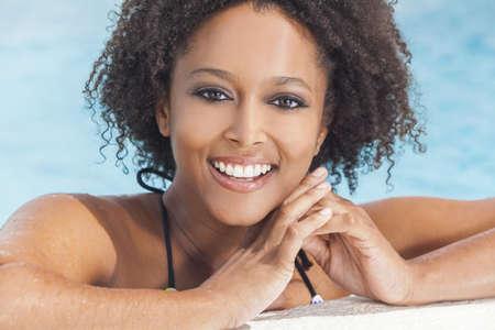 Una hermosa sexy joven mujer afroamericana niña o joven que llevaba un bikini y relajante en el lado de una piscina.
