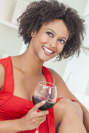 A beautiful happy mixed race African American girl or young woman wearing a red dress and drinking red wine at home Stock Photo - 17286188