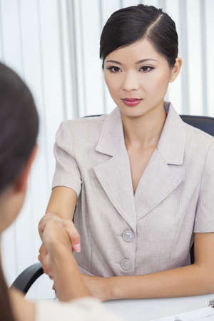 Portrait of a beautiful young Asian Chinese woman or businesswoman in office meeting with female colleague shaking hands securing a handshake deal agreement photo