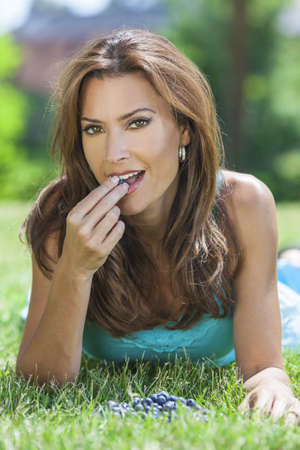 laying down: A beautiful woman in her thirties laying down outside on grass holding or eating blueberries fruit