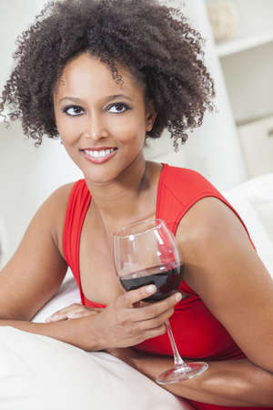 A beautiful happy mixed race African American girl or young woman wearing a red dress and drinking red wine at home Stock Photo - 17329941