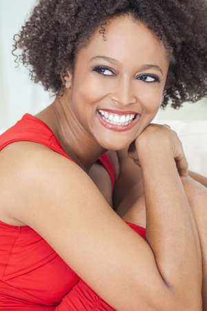perfect teeth: A beautiful mixed race African American girl or young woman wearing a red dress looking happy and smiling with perfect teeth
