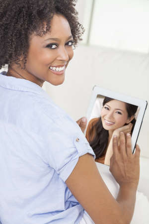 Beautiful happy mixed race African American woman or girl at home sitting on her sofa   smiling using a tablet computer for a video call to her Asian Chinese female friend Stock Photo - 17329570