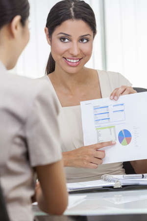 Portrait of a beautiful young mixed race Hispanic woman or businesswoman in office meeting with female colleague using a graph of figures or statistics Stock Photo - 17329937