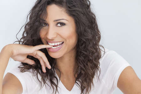 perfect teeth: Studio portrait of a beautiful young mixed race Latina Hispanic woman smiling and biting her finger with perfect teeth Stock Photo