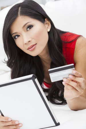 Beautiful Asian Chinese woman using a credit card to shop on the internet with a tablet computer photo