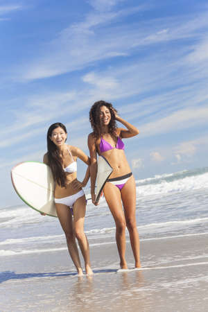 Beautiful young women surfer girls in bikinis with surfboards standing in the sea laughing on a sunny beach Stock Photo - 17475677