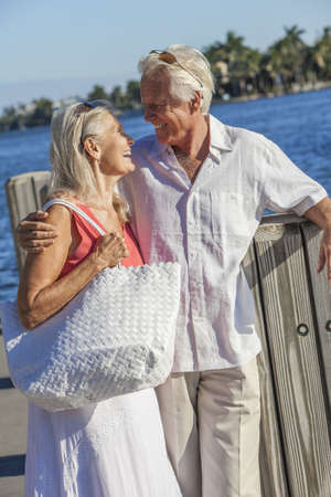 Happy senior man and woman romantic couple together embracing walking by tropical sea or river with bright clear blue sky Stock Photo - 17475686