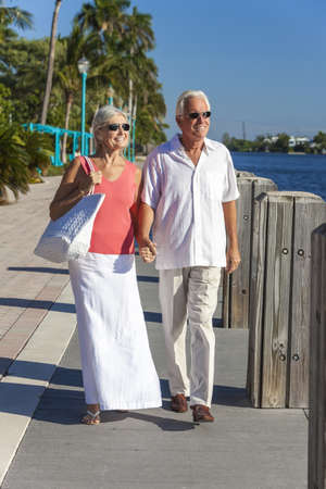 Happy senior man and woman romantic couple together looking out to tropical sea or river with bright clear blue sky Stock Photo - 17475676