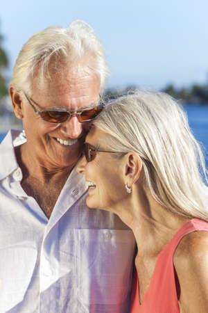 Happy senior man and woman romantic couple laughing together next to tropical sea or river with bright clear blue sky Stock Photo - 17475681