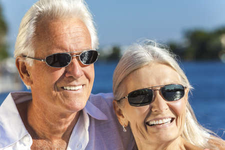 Happy senior man and woman romantic couple together looking out to tropical sea or river wearing sunglasses Stock Photo - 17475678