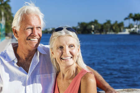 Happy senior man and woman romantic couple together looking out to tropical sea or river with bright clear blue sky Stock Photo - 17475685