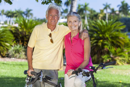 Happy senior man and woman couple together cycling on bicycles in a sunny green park Stock Photo - 17544338