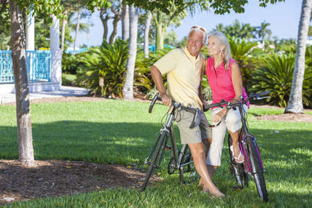 Happy senior man and woman couple together cycling on bicycles in a sunny green tropical park Stock Photo - 17544341