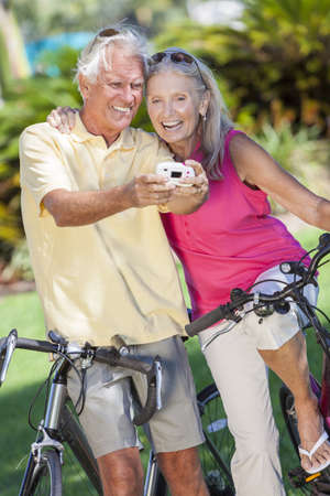 Happy senior man and woman couple together cycling on bicycles taking self portrait picture photograph with digital camera in a sunny green park Stock Photo - 17544333