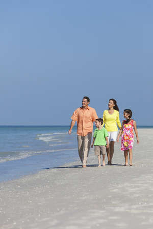 A happy family of mother, father and two children, son and daughter, walking holding hands and having fun in the sand of a deserted sunny beach Stock Photo - 17544336