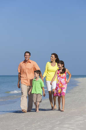 A happy family of mother, father and two children, son and daughter, walking holding hands and having fun in the sand of a deserted sunny beach Stock Photo - 17544334