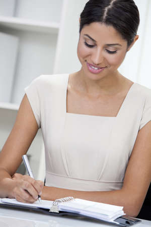 Beautiful young mixed race, Latina Hispanic woman or businesswoman in smart business suit sitting at a desk in an office writing in her diary Stock Photo - 17544331