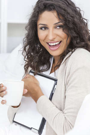 Beautiful young Latina Hispanic woman laughing, relaxing, using a tablet computer and drinking tea or coffee Stock Photo - 17544332