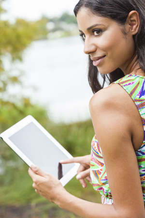 Happy, smiling, beautiful mixed race Latina Hispanic young woman or girl outside using tablet computer Stock Photo - 17544330