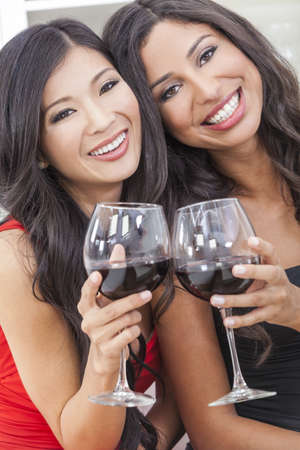 Two beautiful young women friends, Asian Chinese and Hispanic having fun drinking red wine together Stock Photo - 17758207