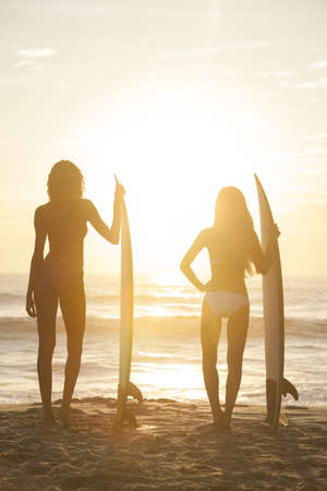 Rear view of two beautiful sexy young woman surfer girls in bikinis with white surfboards on a beach at sunset or sunrise photo