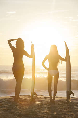 Beautiful young women surfer girls in bikinis with surfboards on a beach at sunset or sunrise Stock Photo - 17758192