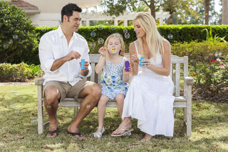 A young family mother & father parents with girl child blowing bubbles having fun together sitting on a bench in a sunny park or garden. photo