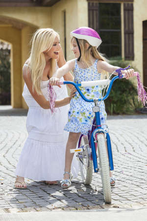 Young girl child riding a bicycle with her happy excited mother parent giving encouragement alongside her photo